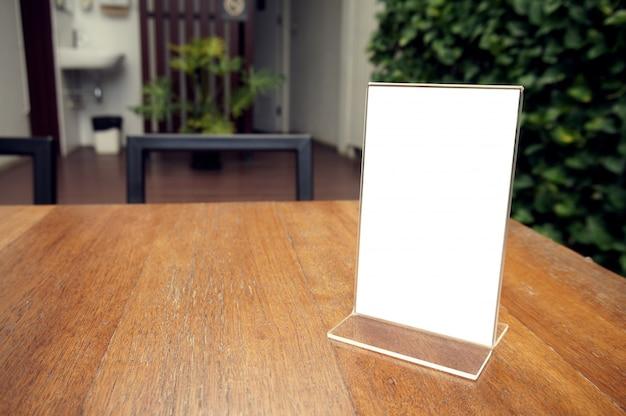 モックアップバーレストランカフェの木製テーブルに立つメニューフレーム。テキストのスペース。