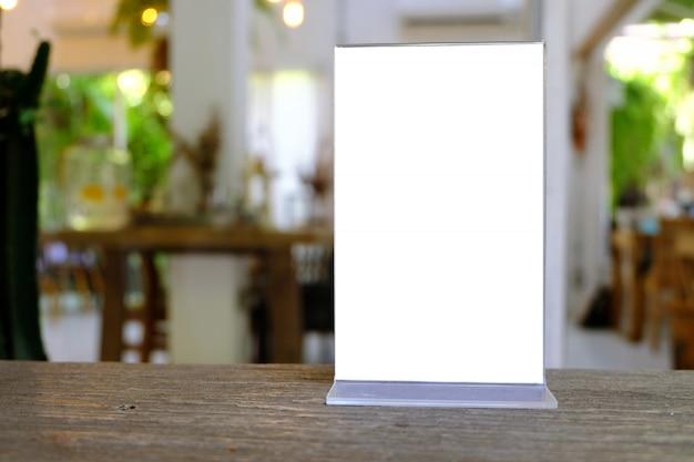 Макетная рамка меню, стоящая на деревянном столе в кафе-баре ресторана