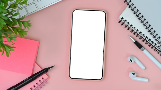 Mock up mobile phone with blank screen, wireless earphone, notebook and sticky note on pink background. flat lay