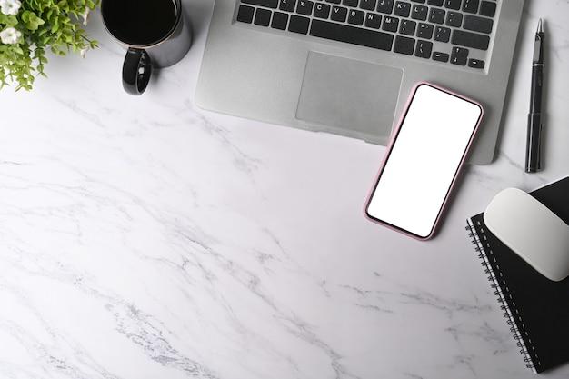 Копируйте мобильный телефон с пустым экраном, портативным компьютером и чашкой кофе на мраморном фоне.