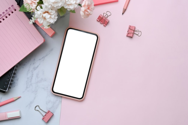 Копируйте мобильный телефон с пустым экраном на розовом и мраморном фоне.