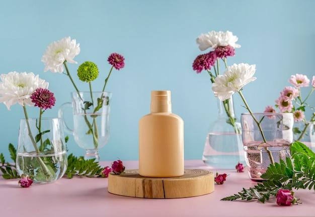 自然化粧品のモックアップ:花で青い背景に広告するための美容液、クリーム、マスク。有機製品。スパのコンセプト。