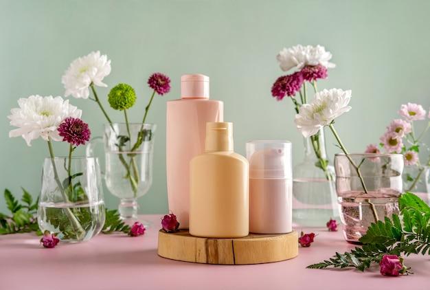 Макет натуральной косметики: сыворотка, крем, маска для рекламы на зеленом фоне с цветами. органические продукты. концепция спа
