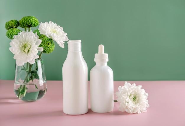 自然化粧品のモックアップ:花のある緑の背景に広告を出すための美容液、クリーム、マスク。有機製品。スパのコンセプト