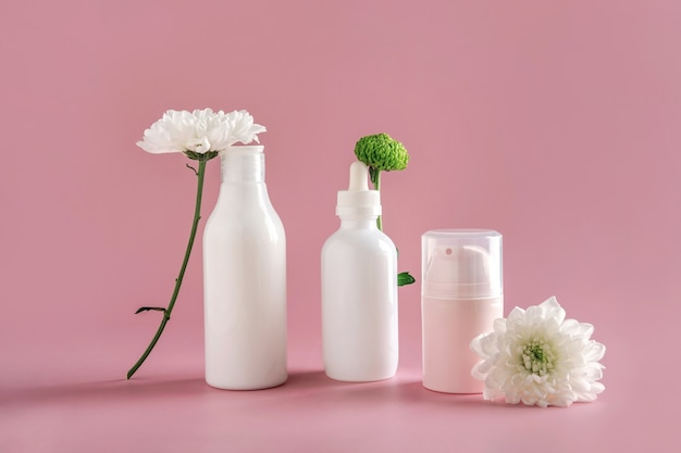 自然化粧品のモックアップ:花のある淡いピンクの背景に広告を出すための美容液、クリーム、マスク。有機製品。スパのコンセプト