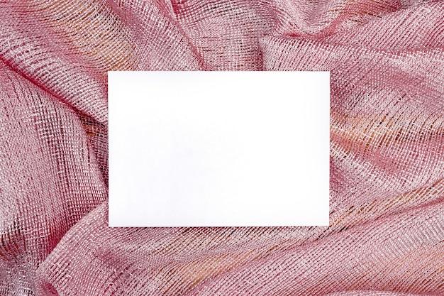 ピンクの布に白紙のモックアップ。デザイン用の紙のテンプレート。名刺。フラットレイ、コピースペース