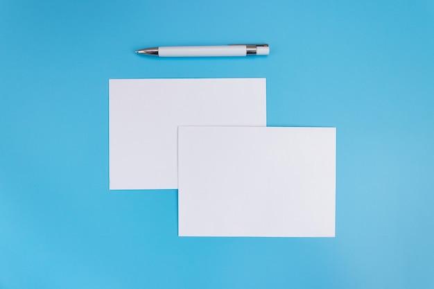 ペンで青い背景に白紙のモックアップ。デザイン用の紙のテンプレート。名刺。フラットレイ、コピースペース。