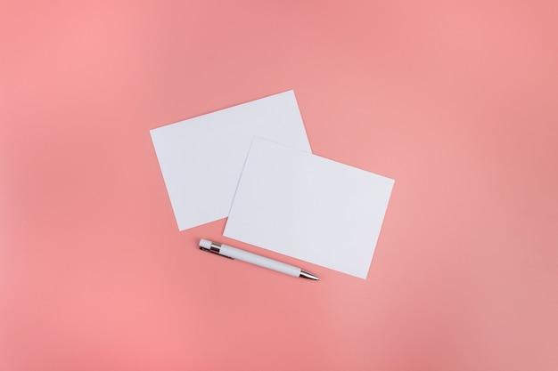ペンで珊瑚の背景に白紙のモックアップ。デザイン用の紙のテンプレート。名刺。フラットレイ、コピースペース