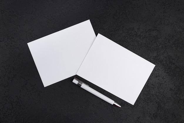 ペンで暗いコンクリートの背景に白紙のモックアップ。デザイン用の紙のテンプレート。名刺。フラットレイ、コピースペース