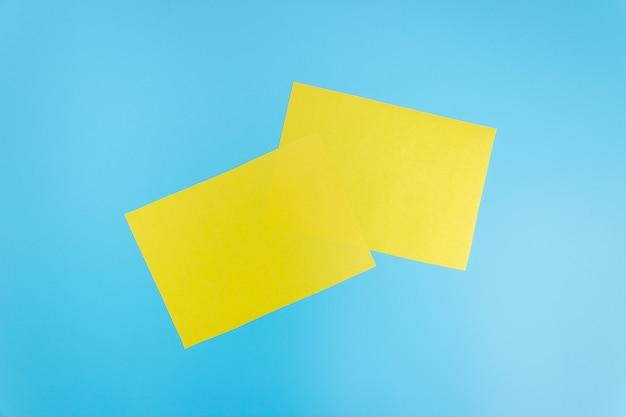 青い背景に空白の黄色いシートのモックアップ。デザイン用の紙のテンプレート。名刺。フラットレイ、コピースペース