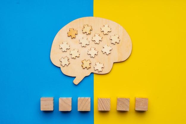 黄色と青の背景に散らばったパズルのピースで人間の脳のモックアップ。フォントに自閉症という言葉を書くことができる6つの立方体。