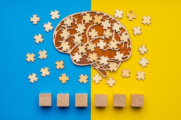 黄色と青の背景に散在するパズルのピースで人間の脳のモックアップ。フォントに自閉症という言葉を書くことができる6つの立方体。