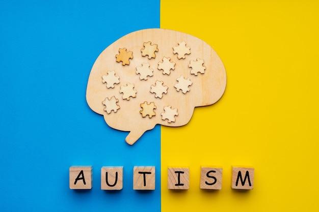 黄色と青の背景に散在するパズルのピースで人間の脳のモックアップ。自閉症の碑文を持つ6つの立方体。