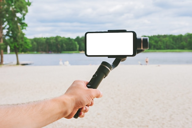 한 남자의 손에 카메라 안정기가 있는 스마트폰을 비웃습니다. 모래 해변과 호수가 있는 자연을 배경으로.