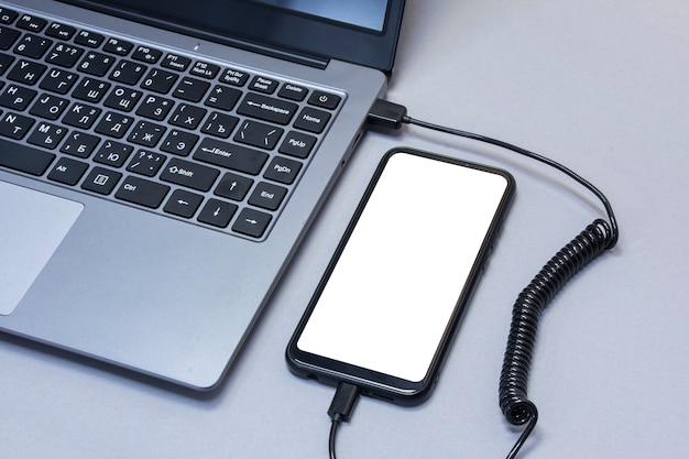 회색 테이블 배경에 노트북에서 충전되는 흰색 화면 클로즈업 스마트 폰의 모형.