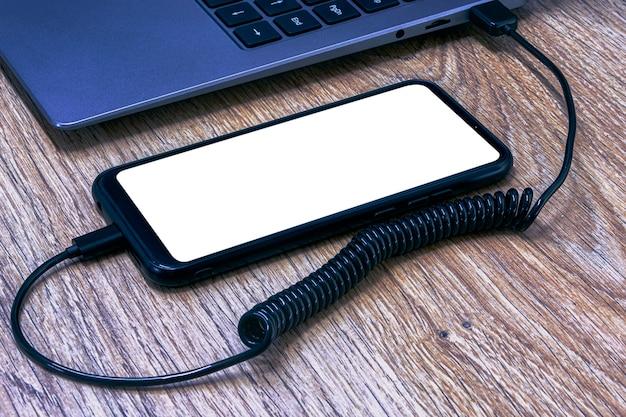 나무 테이블 배경에 노트북에서 충전되는 흰색 화면 클로즈업 스마트 폰의 모형.