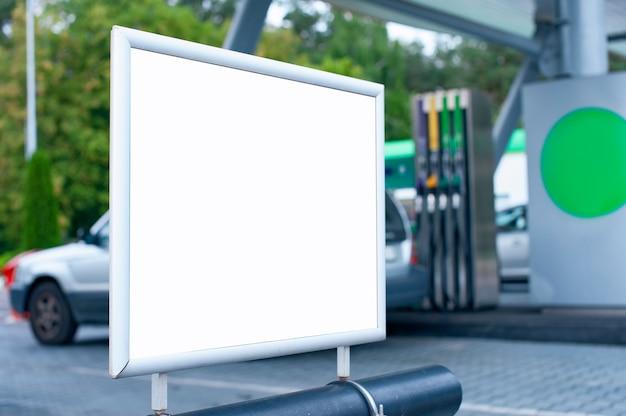 車とガソリンスタンドを背景にした白い看板のモックアップ。