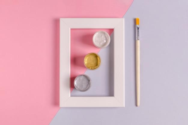 3 가지 색상의 아크릴 페인트 캔과 장식 및 페인팅을위한 브러시가있는 흰색 빈 프레임을 모의합니다. 핑크와 라일락 배경, 미니멀리즘. 선택적 초점.