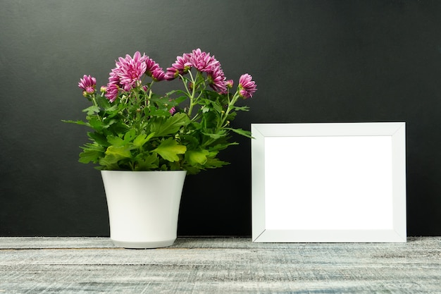木製のテーブル、黒い壁の白い鍋に花と白いフレームのモックアップ。縦向き