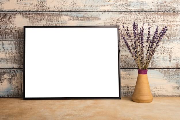 木の板の壁に空のフレームのポスターのモックアップ。花瓶にラベンダーの束