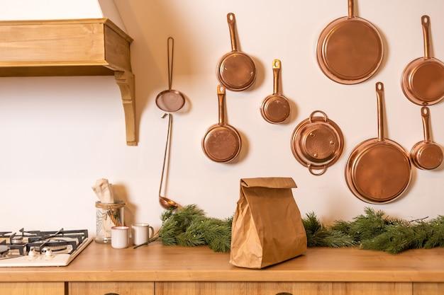 손잡이가 있는 큰 갈색 종이 패키지, 로고나 디자인을 위한 공간이 있는 빈 공예품 쇼핑백, 배경의 흰색 벽, 음식 배달 개념