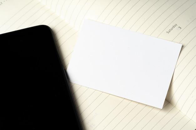 Макет пустой визитной карточки и черный экран смартфона на столе
