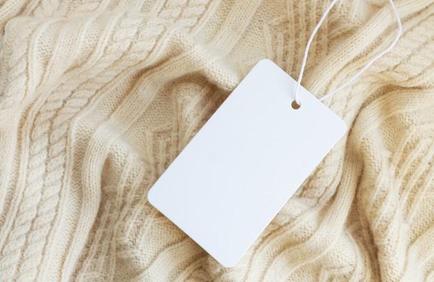 Макет пустой белой бумаги ценник или этикетка на теплом фоне крупным планом свитера