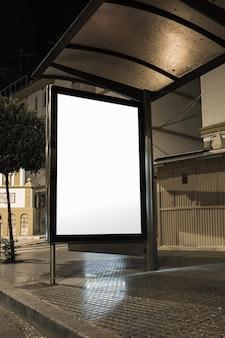밤에 도시에서 버스 정류장에 빈 흰색 세로 라이트 박스를 조롱