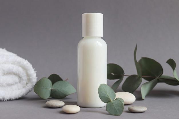 유칼립투스 잎이 있는 흰색 튜브에 몸과 얼굴 크림을 비웃다 뷰티 스파와 화장품