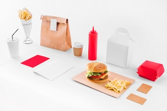 Mock up of burger; french fries; parcel; sauce bottle and disposal cup on white backdrop