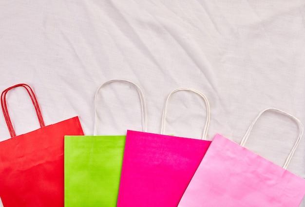 다채로운 가방, 흰색 배경에 패키지, 상위 뷰 및 텍스트, 쇼핑 및 라이프 스타일 개념, 평면 배치에 대한 복사 공간을 모의합니다.