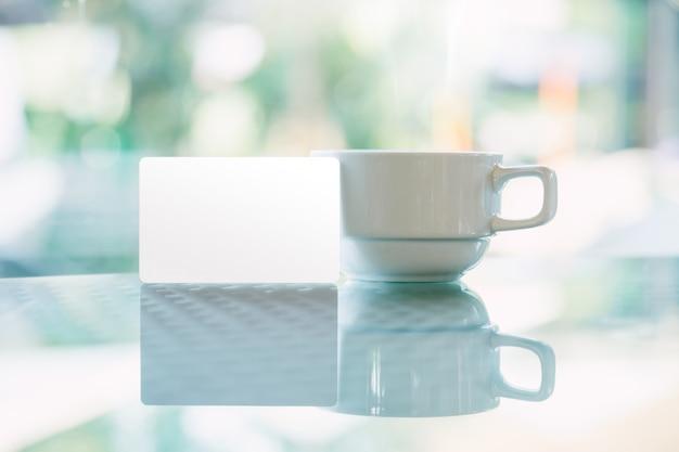 コーヒーカップの近くに置かれたクレジットカードのモックアップ