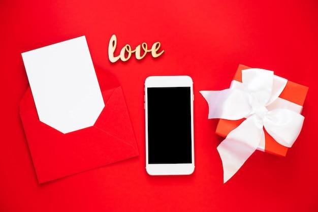 封筒にスマートフォンとグリーティングカードのモックアップ。バレンタインデーまたは母の日のテンプレート。