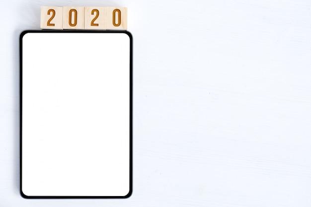 タブレット、新年を象徴する数字を持つキューブのモックアップ