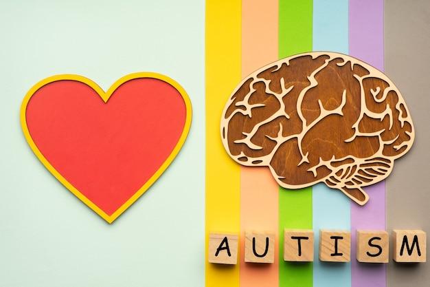 カラフルな背景に人間の脳と心臓のモックアップ。自閉症の碑文を持つ6つの立方体。