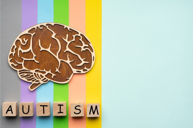 カラフルな背景に人間の脳のモックアップ。自閉症の碑文を持つ6つの立方体。