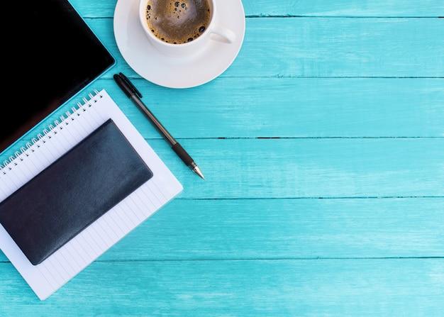 Насмешка белой чашки кофе, черной тетради, тетради, ручки и таблетки на бирюзовом деревянном столе.