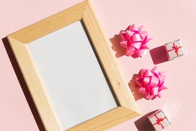 ポスターとギフトボックスのコピースペース付き木製フレームのモックアップ、ピンクの背景にピンクのサテンの弓。母の日、女性の日または他の適切なホリデーカード、テキストのコピースペース付きフォトフレーム