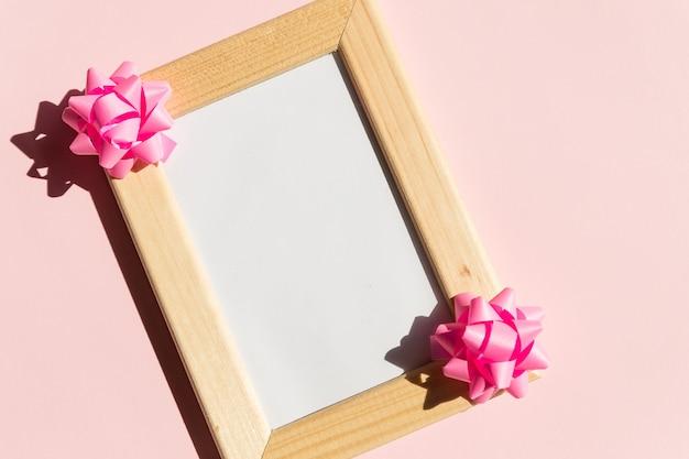 ポスターとギフトボックスのコピースペースを持つ木製フレームのモックアップ、ピンクの背景にサテンの弓。ピンクのリボンの弓、誕生日、結婚式やバレンタインデーのフレームのモックアップ。休日のグリーティングカード