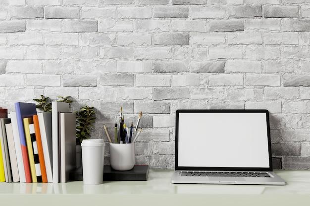 노트북 빈 화면으로 작업 영역을 비웃는 다. 사무실 테이블과 벽 흰색 벽돌 배경에 노트북 흰색 화면.