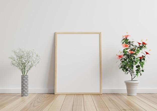 Макет фоторамки в комнате, белая стена на деревянном полу, украшенная растениями с каждой стороны. 3d-рендеринг.