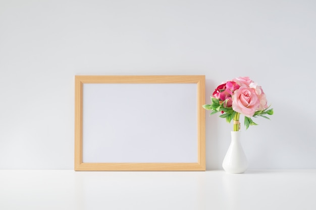 Mock up photo frame with flowers on table