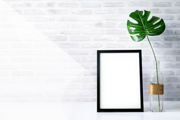 Mock up portrait photo frame with green plant on tabl