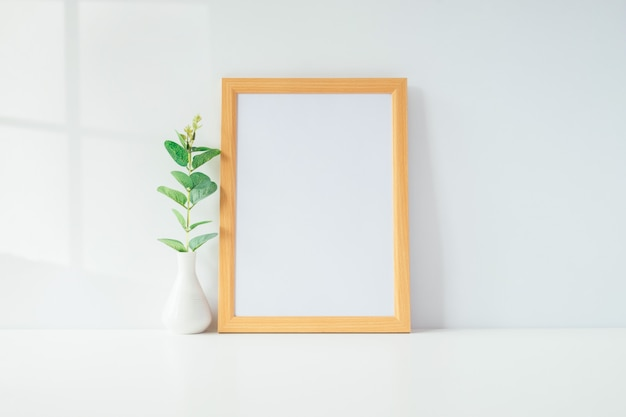 Mock up portrait photo frame with green plant on table, home decoration.