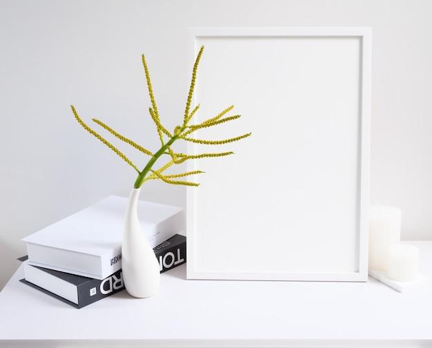 白いテーブルとセメントの壁の背景にモダンな花瓶とキャンドルで黄色のヤシや蝶のヤシの花の構成でポスターフレームの黒と白の本をモックアップ