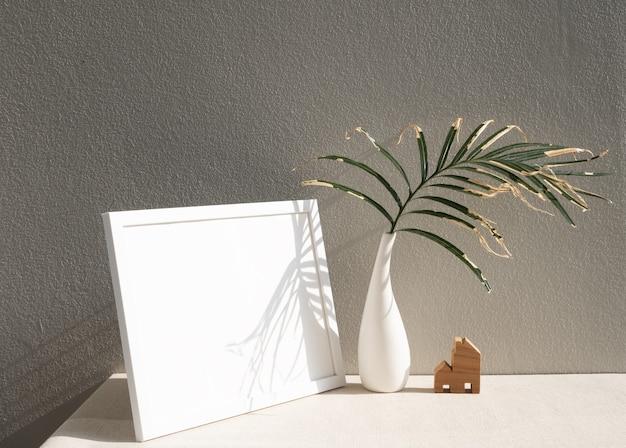 美しい白いセラミックの花瓶にポスターフレームの家のモデルと乾燥したヤシの葉をモックアップ