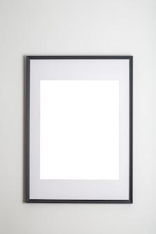 ポスターまたは写真画像の内部の白い壁の白いフレームにポスターフレームをモックアップします。