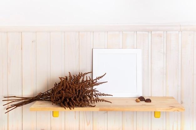 마른 나무 선반에 포스터 프레임을 모의