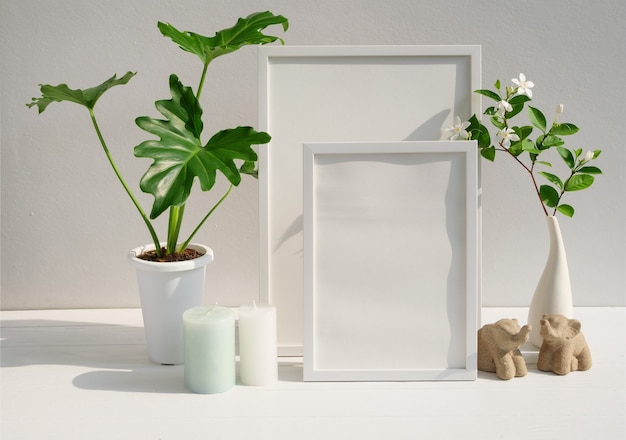 Mock up poster frame philodendron plant gardenia flower in modern white vase  candle and elephants stasue  on spa  table and cement wall surface with long shadow