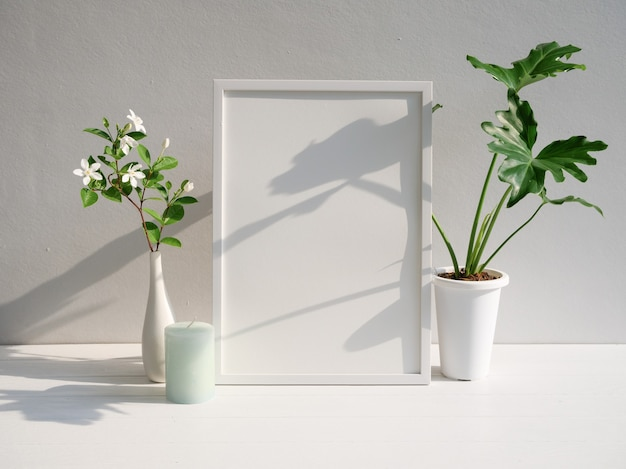 Mock up poster frame philodendron selloum gardenia flower  in modern white vase  and green candle  on white wood  table and cement wall background with long shadow